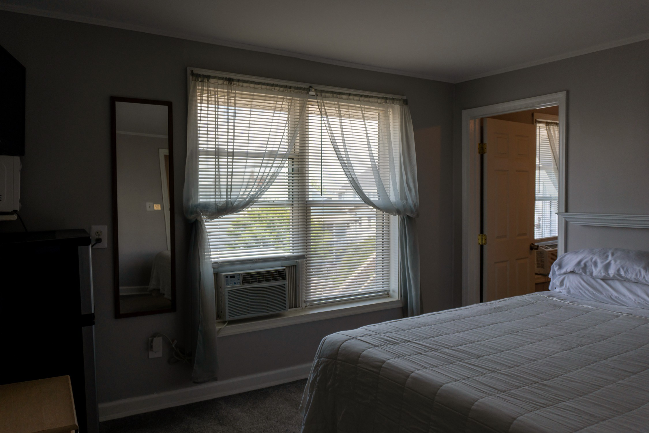 bedroom with queen bed, dresser, and window with a/c unit