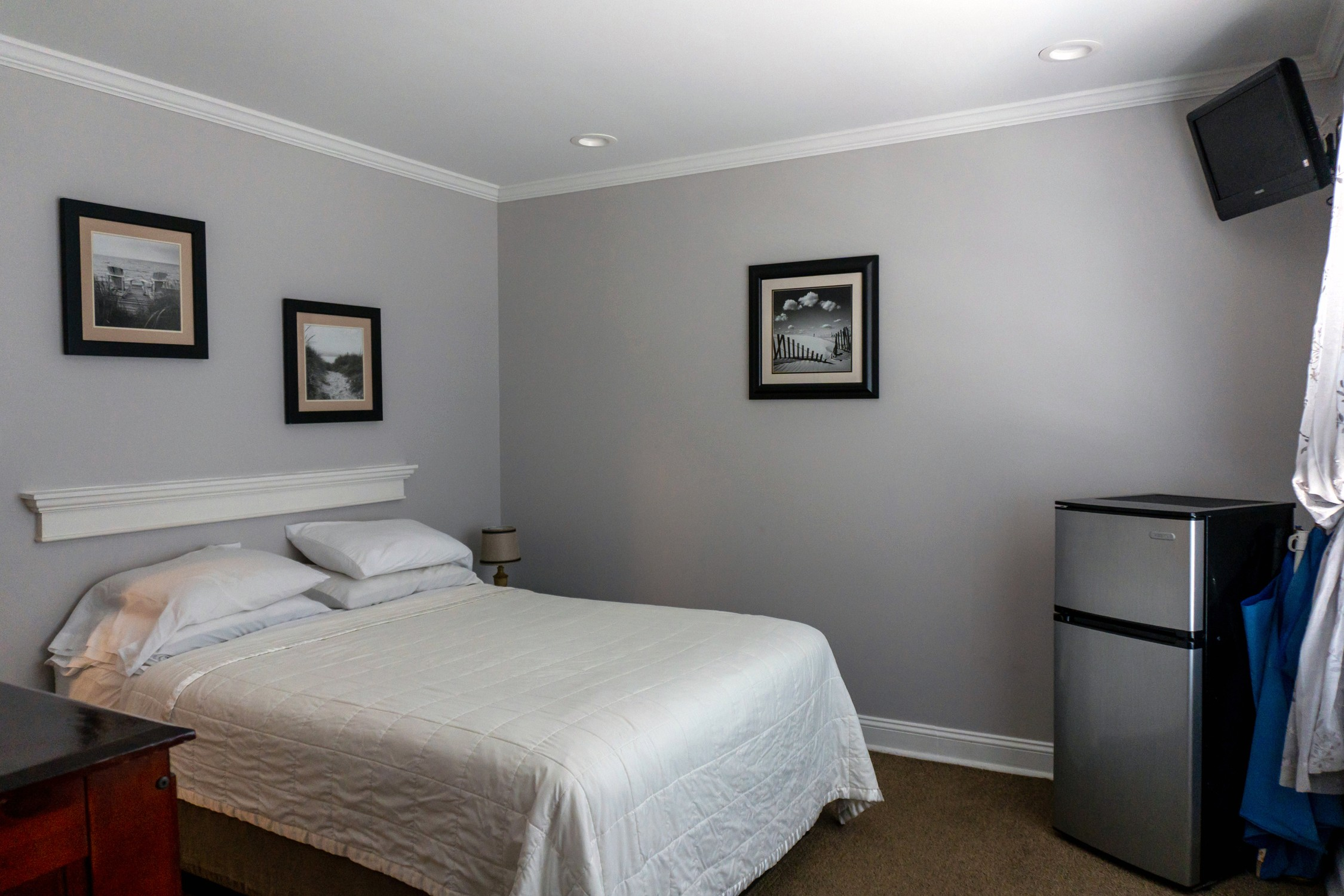 room with 1 queen bed, mounted flat screen tv, and mini fridge