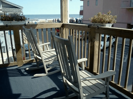 porch with chair and rocking chair with boardwalk and ocean view
